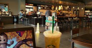 Inside of a coffee shop with drinks, laptop and customers